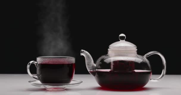 Glass cup with hot hibiscus tea and teapot on table against dark background