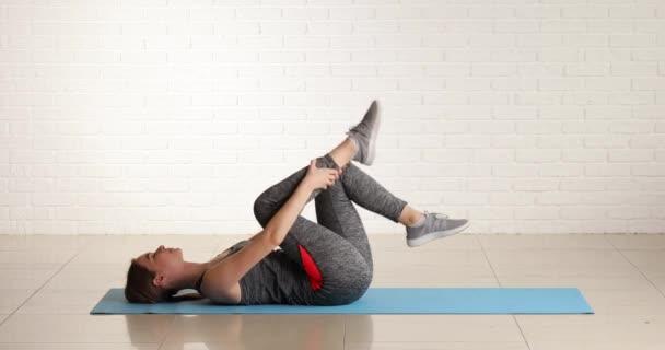Sportovní mladá žena dělá pilates v tělocvičně