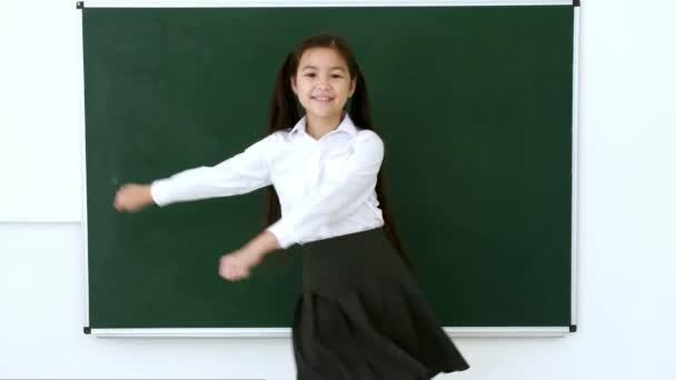 Vicces kis iskolás lány táncol az osztályteremben.