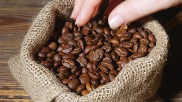 Samičí ruka s taškou plnou pražených kávových zrn na stole