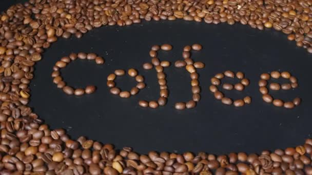 Rotating dark board with word COFFEE made of roasted beans