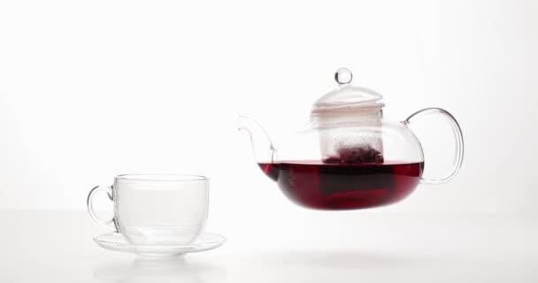 Nalití horkého ibiškového čaje ve skleněném šálku na bílém pozadí