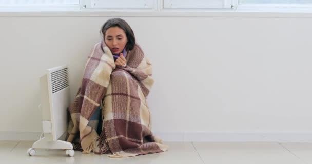 Mladá žena zabalená v teplém kostkovaném sedí v blízkosti zapnuto elektrické topení v pokoji