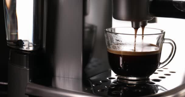 Nalití horkého nápoje z kávovaru do skleněného kelímku, detailní záběr