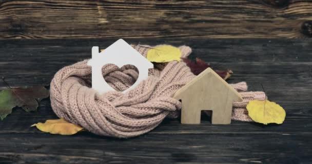Häuserfiguren, warmer Schal und Herbstblätter auf hölzernem Hintergrund. Konzept der Heizsaison