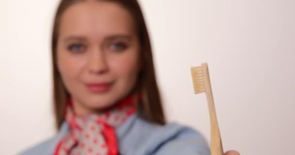 Junge Frau mit Zahnbürste auf hellem Hintergrund