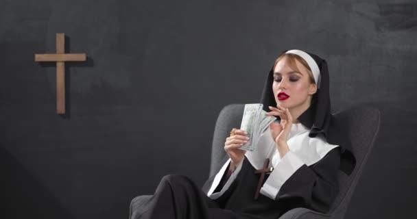 Sexy jeptišky počítání peněz, zatímco sedí v křesle na tmavém pozadí