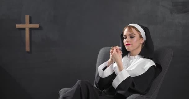 Sexy jeptiška s drahými šperky sedí v křesle na tmavém pozadí
