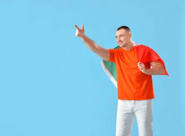 Young man with Mexican flag pointing at something on color background