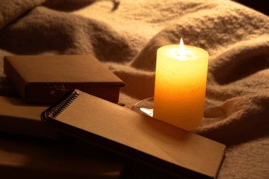 Burning candle and books on fabric in room