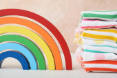 Stylish baby clothes with rainbow on color background