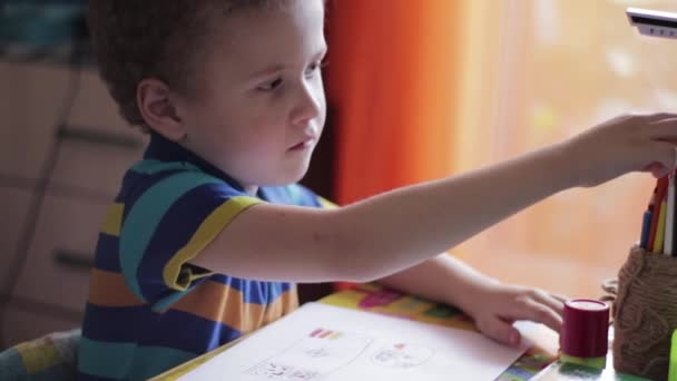 Little boy draws at a table at home. The child is engaged in creativity, studying at home, video
