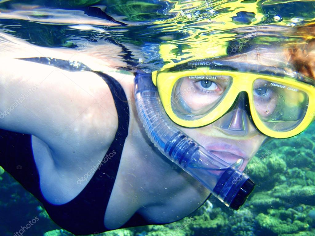 The girl in a mask with a tube under water (snorkeling).