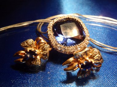 Gold earrings and pendent with sapphires on blue macro