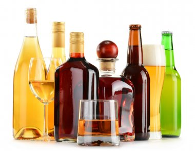 Bottles and glasses of assorted alcoholic beverages over white
