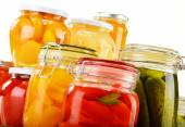 Photo Jars with pickled vegetables, fruity compotes and jams isolated