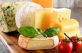 Různé druhy sýra, izolované na kuchyňském stole
