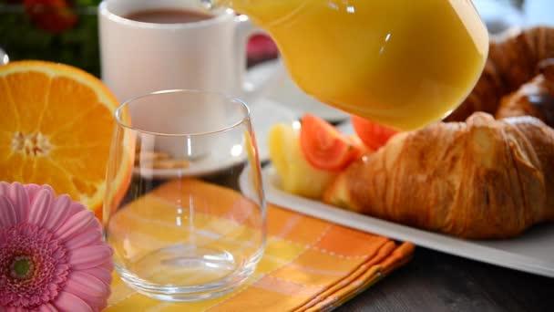 Töltés pohár narancslé a reggeli asztal