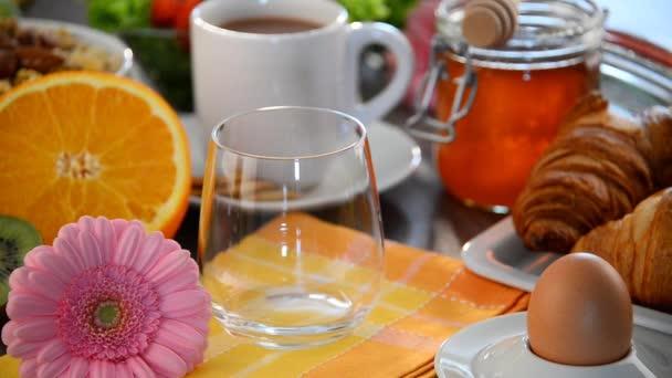 Vyplňování skla s džusem stolu se snídaní