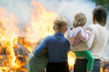 Mother with children at burning house background