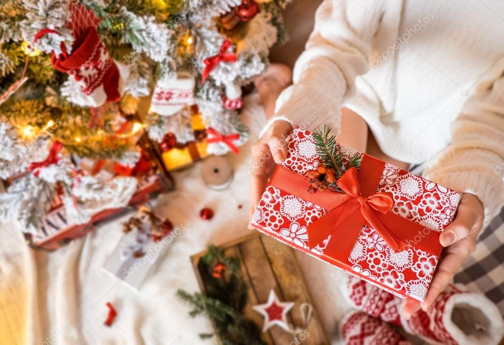 Young pretty woman in warm cozy clothes is sitting on the light wooden floor in her bright house near the christmas tree and holds gift box in her hands.