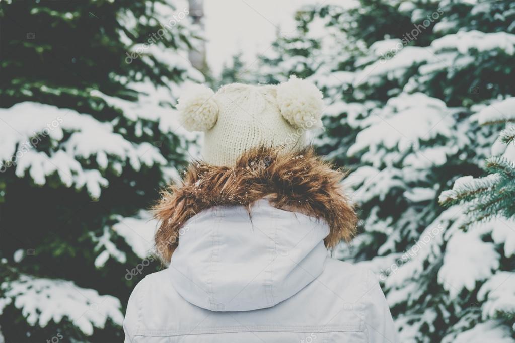 Фотообои Молодая женщина в вязаной шапке проходит между елочек в лесу.