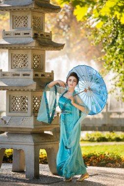 beautiful geisha with a blue umbrella near stone pagoda