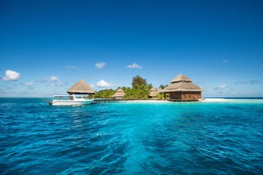 small tropical island with Beach Villas and speed boat