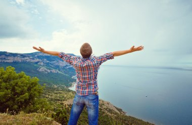 guy on top of a mountain with arms outstretched