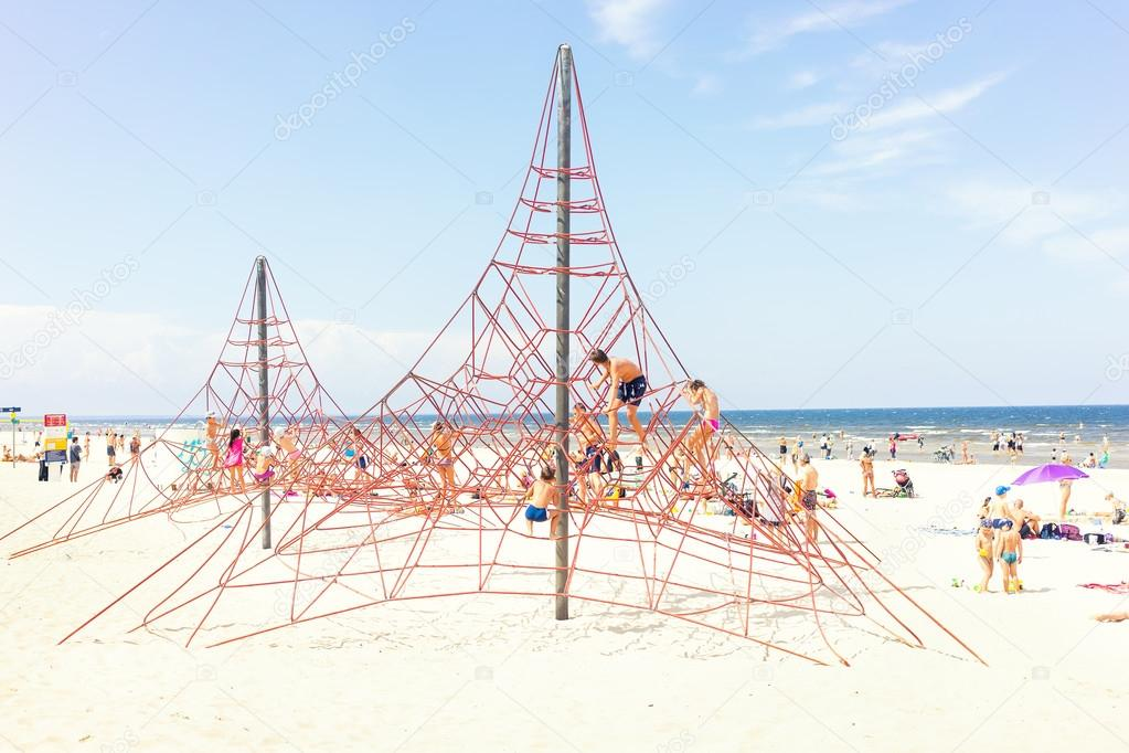 Children in the summer on the beach by the sea climb ropes