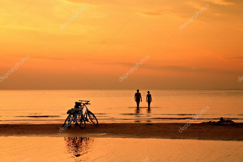 The couple is swimming in the sea at sunset on background of bic