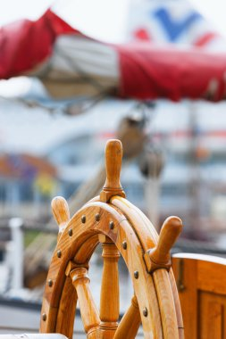 Steering wheel on the boat sails in port