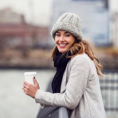 Beautiful smiling woman drinking coffee from paper cup standing on river embankment and enjoing the view
