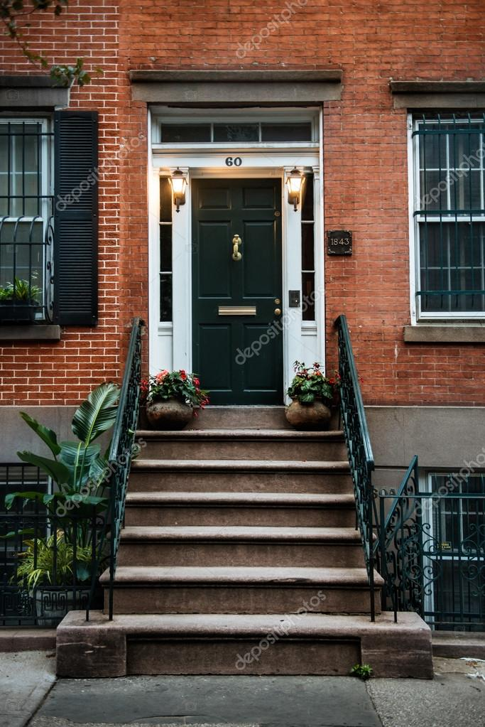 Front Door of a Beautiful Georgian Era English Manhattan Town House. New York City home building entrance with green door and steps