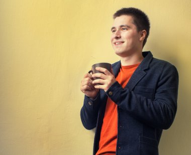 Happy young business man drinking coffee near the wall