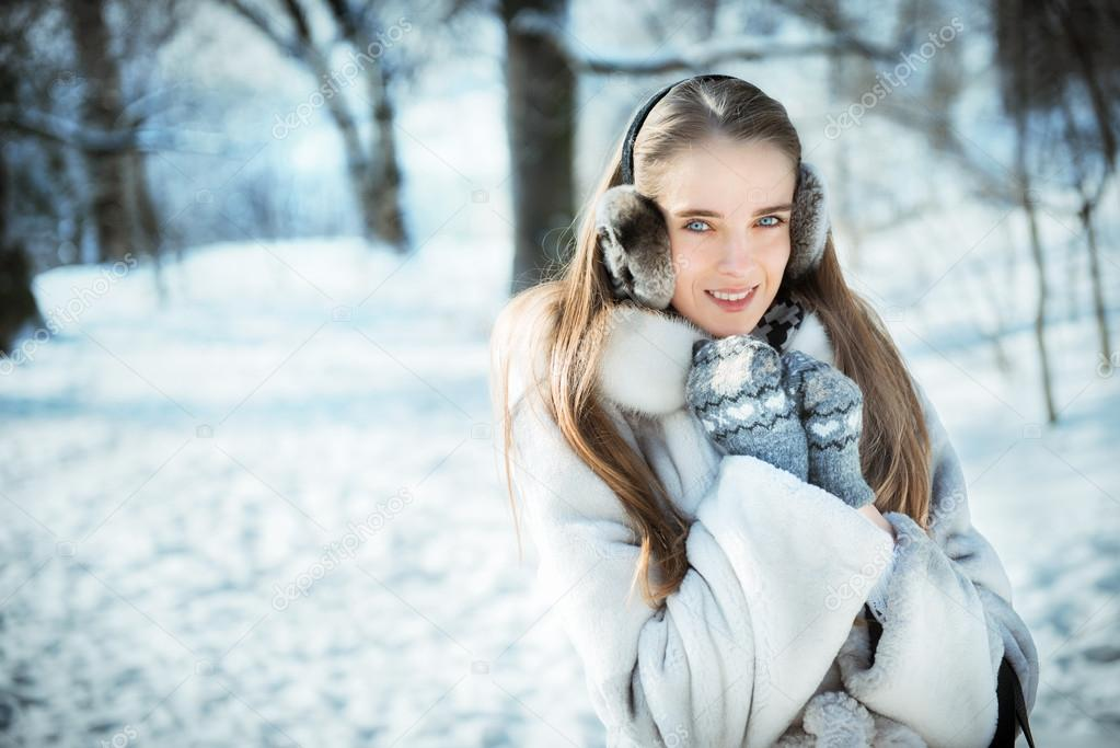 Happy beautiful woman walking in earmuff, knitted mittens and fur coat have fun in winter forest
