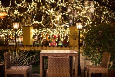 Street cafe at the night agains city illumination lights