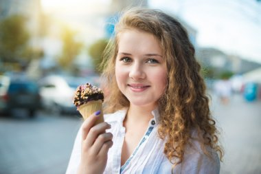 Young girl eating ice cream in the city street