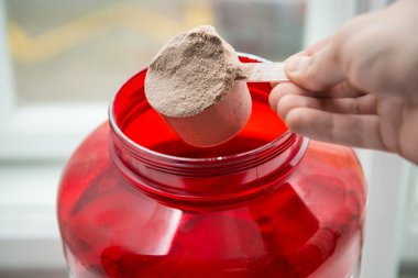 Man taking protein from container by the scoop
