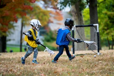 Little kid playing lacrosse with his stick in the autumn park.