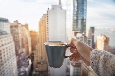 Man holding coffee cup in luxury penthouse apartments with view to New York City Manhattan downtown