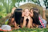 Tři přátelé dívka v jeans kraťasy nad modrá obloha