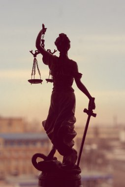 picture of goddess Themis or Lady Justice standing on window holding sword blindfold on the city outdoors background