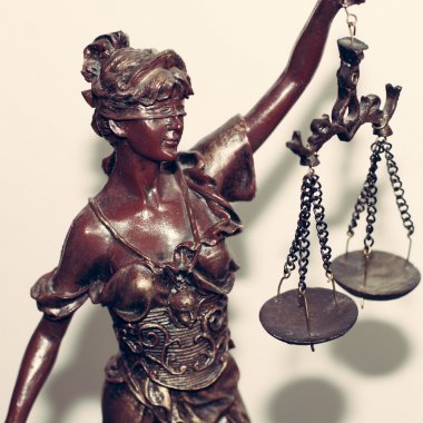 Close up image of lady justice or themis holding scale blindfold on white background