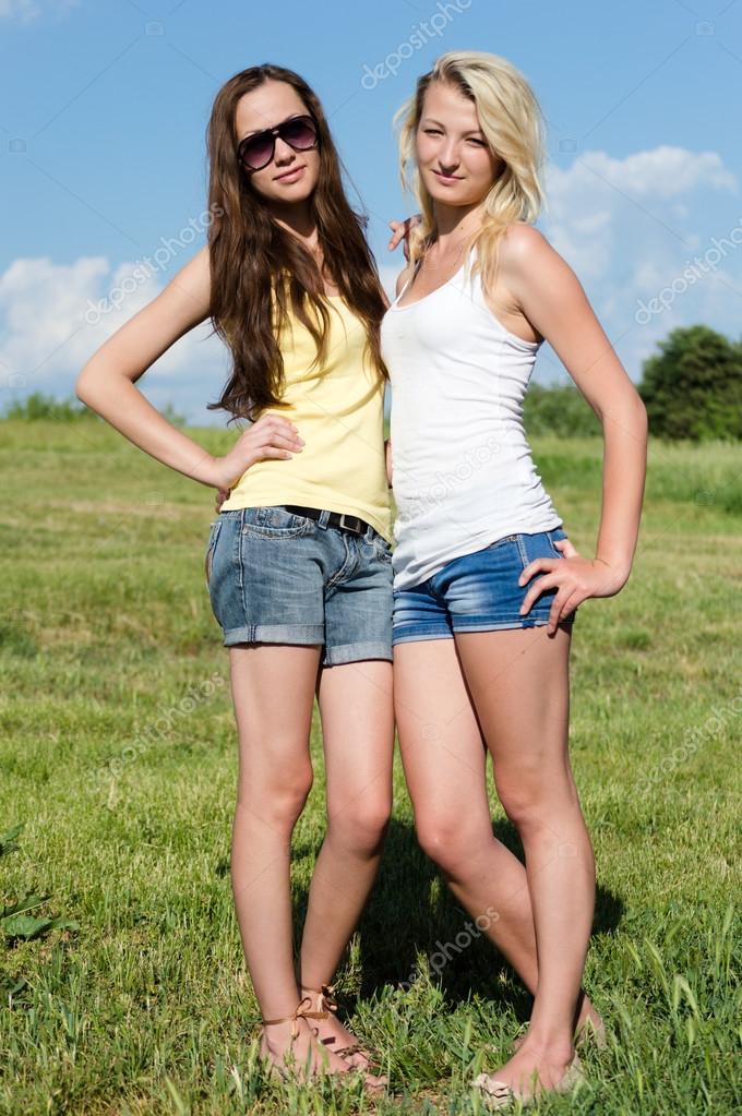 Two girls standing in field
