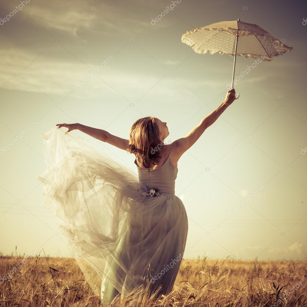Woman in ball dress holding white umbrella
