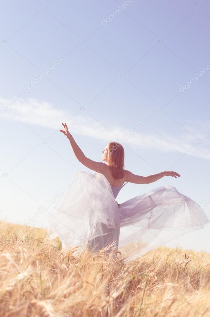 Woman wearing ball dress enjoying outdoors