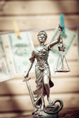 Fotografie Themis goddess or lady justice holding scale blindfold  USD dollar bank notes hanging on the copy space background showing money laundering concept