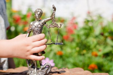 Kid's hand holding sculpture of themis, femida or justice goddess on green leaves natural bokeh background