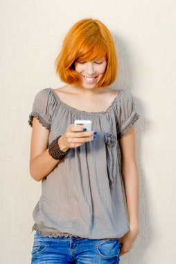 Image of pretty red haired girl having fun reading or using mobile phone happy smiling on light copy space background wall